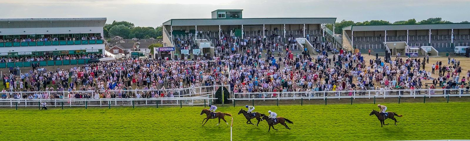 Group of jockeys racing past the grandstand at Great Yarmouth Racecourse.